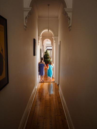 Kids running down a hall towards a Xmas tree Arch Child Childhood Christmas Christmas Tree Hallway Indoors  Long Hallway Rear View Xmas Xmas Decorations Xmas Morning