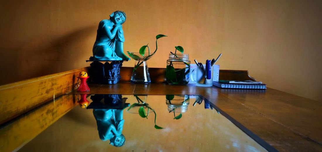 Plant With Pointed Leaves Green Color Blue Buddha Reflection Sclupture Table Glass Arts Culture And Entertainment