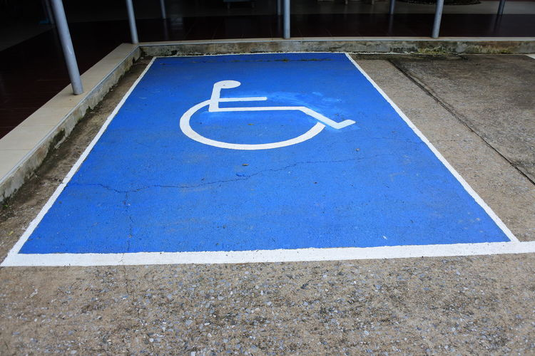 High angle view of wheelchair access sign on parking lot