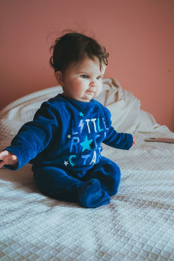 Cute baby girl sitting on bed