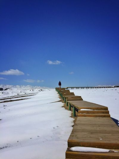 Person walking on pier over snowy landscape against blue sky