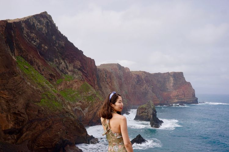 Woman standing against cliff and sea