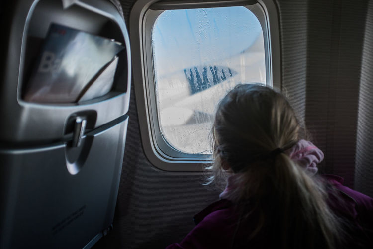 Rear View Of Girl Looking Through Window Of Airplane