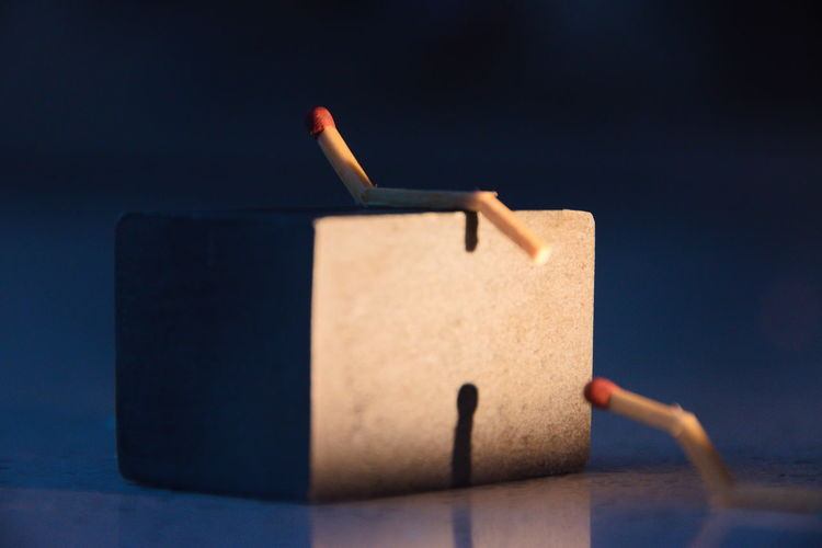 Close-up of block shape with match sticks against colored background