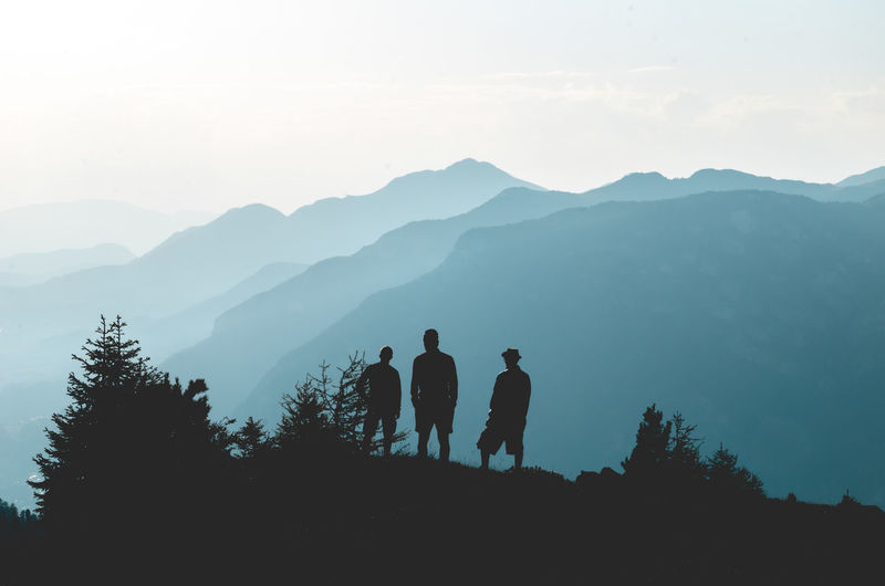Silhouette friends standing by mountains against sky in foggy weather