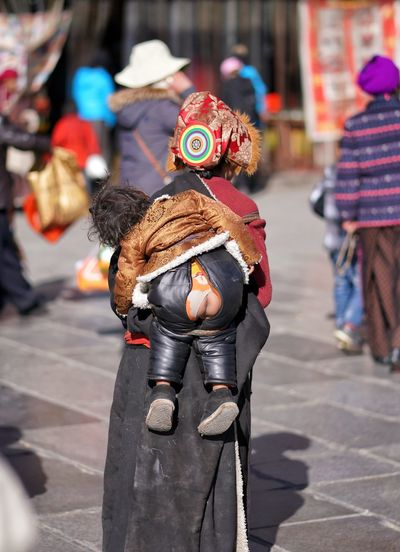 Rear view of mother piggybacking child