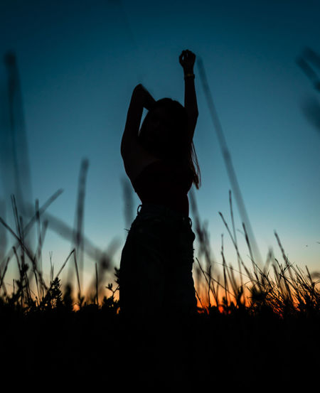 Silhouette woman standing on field against sky during sunset