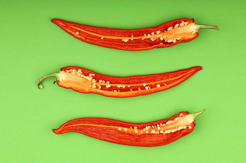 Three halved red hot chili peppers on green background Food And Drink Colored Background Food Studio Shot No People Freshness Pepper Still Life Green Color Green Background High Angle View Healthy Eating Red Spice Close-up Vegetable Chili Pepper Creativity Red Hot Chili Peppers Copy Space Cooking Ingredient Cuisine Art