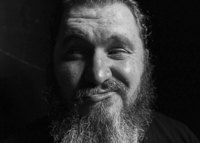 Bearded man making face against black background