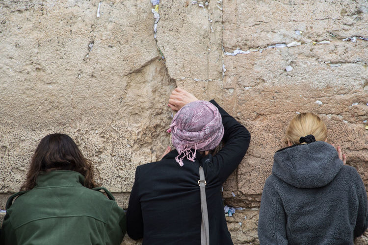 Rear view of women wearing warm clothing while standing against wall