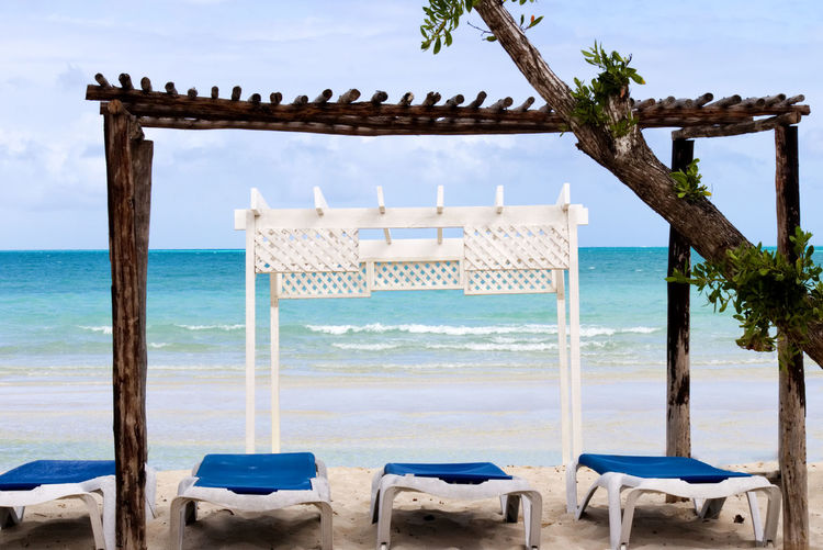Wooden white gazebo by the beach with long chairs under it Water Sea Beach Sky Horizon Nature Tranquil Scene Land Tranquility Horizon Over Water Beauty In Nature Scenics - Nature No People Chair Day Idyllic Vacations Sand Trip Outdoors