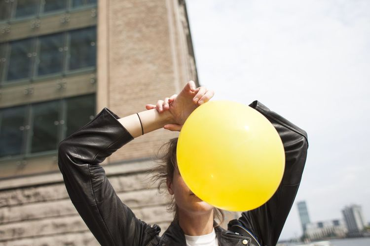 #FREIHEITBERLIN Architecture Balloon Building Exterior Built Structure Day Focus On Foreground Holding Human Body Part Leisure Activity Lifestyles One Person Real People Women Yellow
