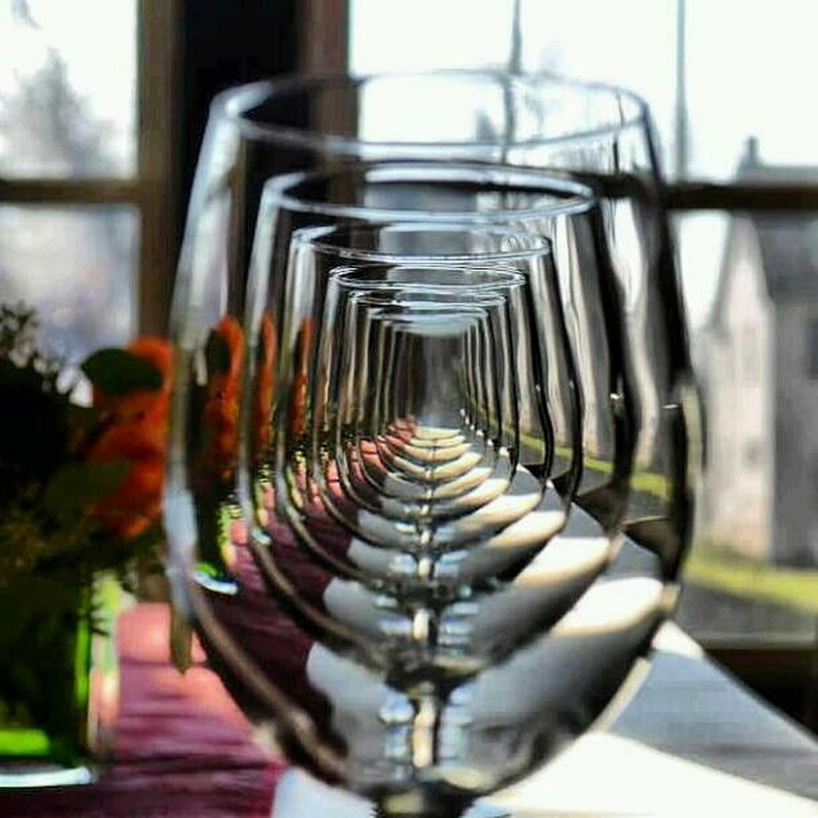 indoors, in a row, focus on foreground, metal, close-up, glass - material, repetition, transparent, hanging, pattern, selective focus, reflection, arrangement, diminishing perspective, empty, railing, no people, day, still life, table