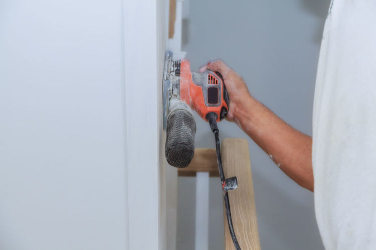 Midsection of man holding sander on wall