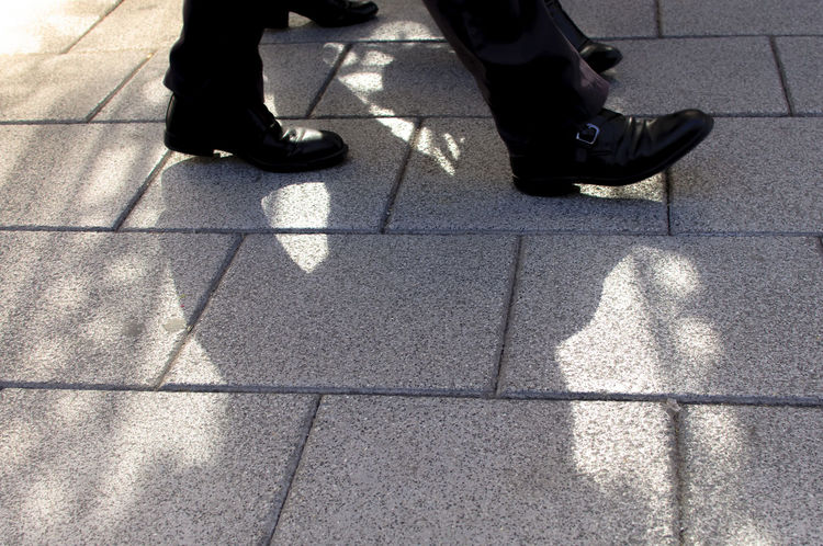 Close up of male pedestrian shoes walking on the pavement with sunshine and patterned shadows in the centre of Madrid. Shoes Street Walking Male Men Shoes Low Section Human Leg Shadow Real People Sunlight Focus On Shadow Only Men Human Foot Human Body Part Sidewalk Outdoors People Day Shoe High Angle View Lifestyles Pattern