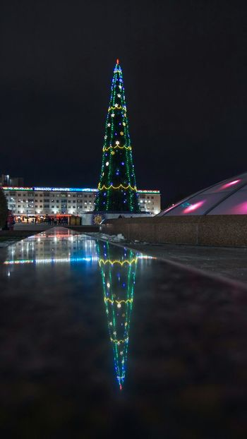 Christmas tree From My Point Of View By Ivan Maximov Eyeem Photo The Week On EyeEm Belarus City Vitebsk,Belarus Great Outdoors Composition Traveling Lights Perspective Holidays New Year Around The World Reflections Night Illuminated Christmas Reflection Christmas Decoration Christmas Tree Christmas Lights Celebration Travel Destinations Architecture Building Exterior No People Outdoors Cityscape City Sky
