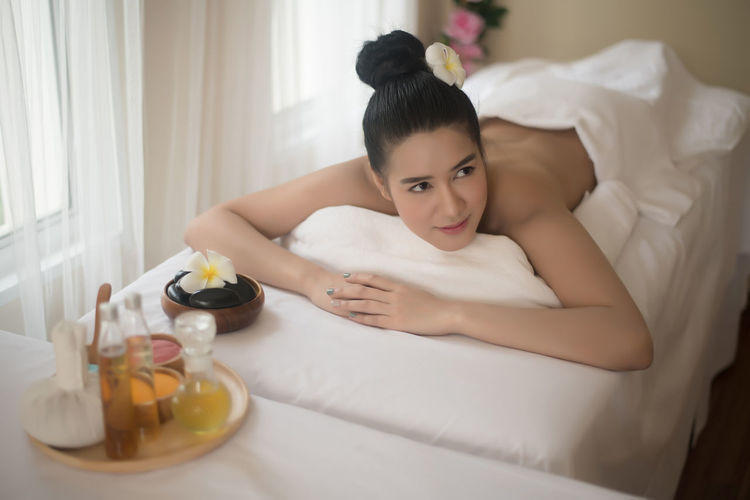 Smiling young woman lying on massage table in spa