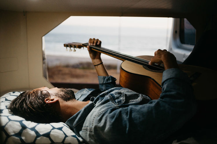 Man Playing Guitar While Lying Down On Bed