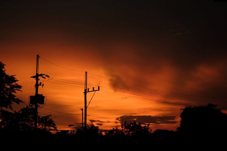 Low angle view of silhouette electricity pylon against dramatic sky