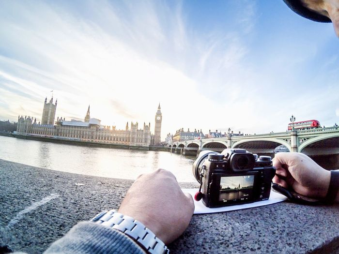 Cropped image of man photographing thames river and big ben through digital camera