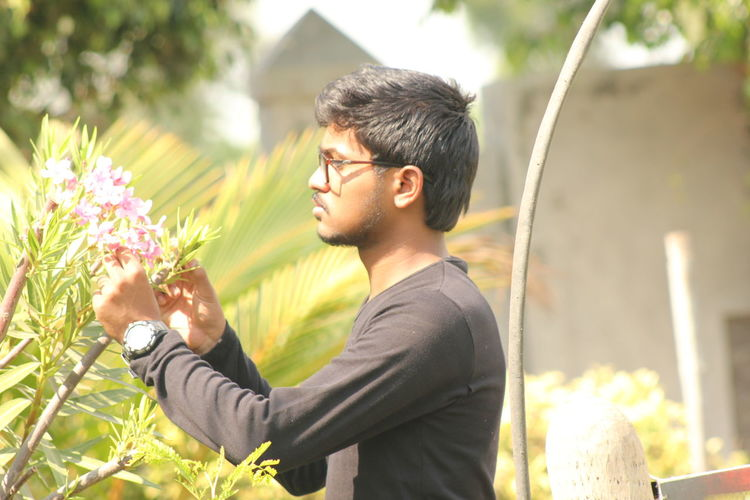 Side view of young man holding flowers