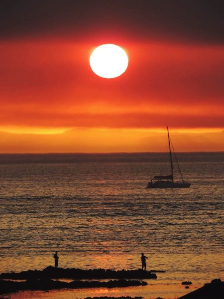 Smoky Sunset Red Sun Yacht Sea Fishermen On Rocks Sea Shore Calm Tranquil