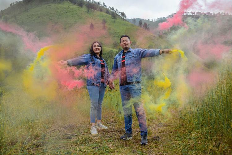 Couple with colorful smoke bombs