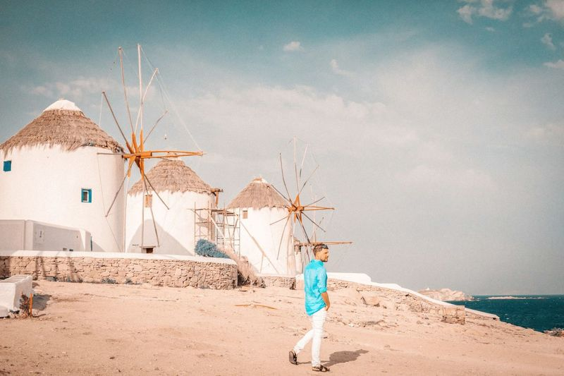 Full length of man walking at beach against sky and traditional windmills