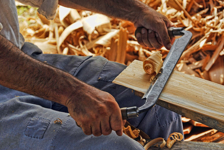 Midsection of man peeling wood at workshop