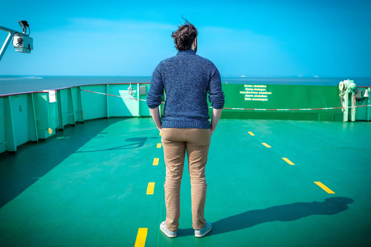 Rear view of woman standing on boat deck in sea against blue sky