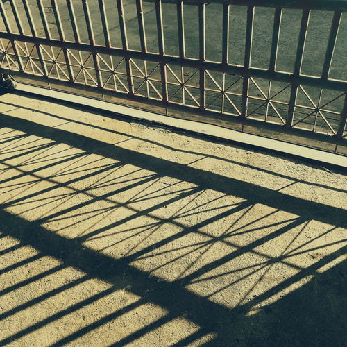 High angle view of sunlight falling on railing