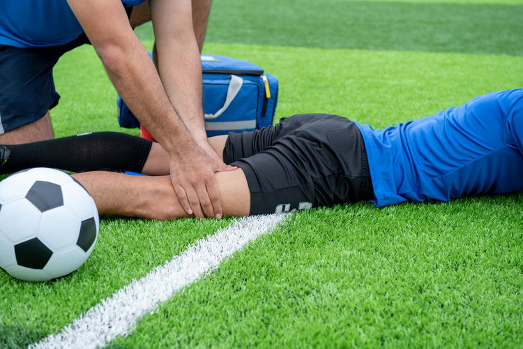 Low Section Of Male Physical Therapist Rubbing Soccer Player Leg On Field