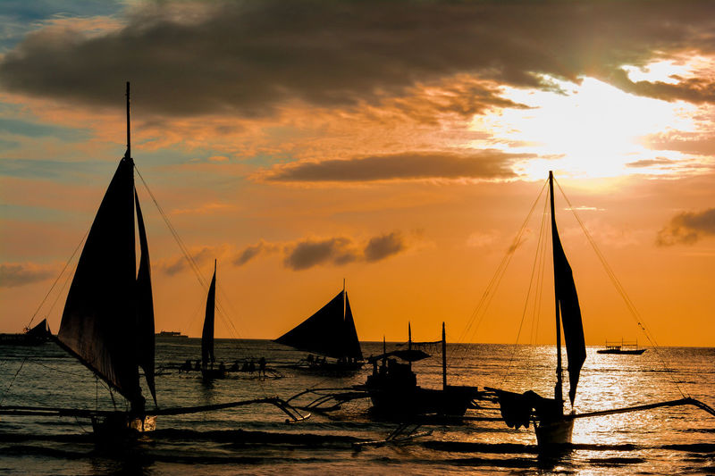 Silhouette Outrigger Sailing Boats On Sea Against Sky During Sunset