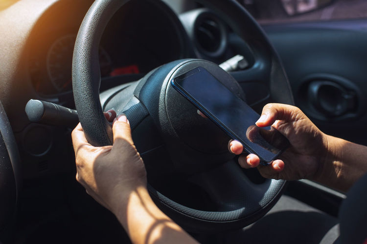 Cropped hands of man using mobile phone while sitting in car