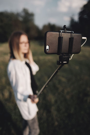 Woman taking selfie through mobile phone while standing on grassy field