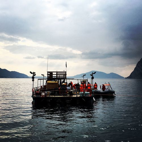 Workers in boat sailing in lake iseo against sky