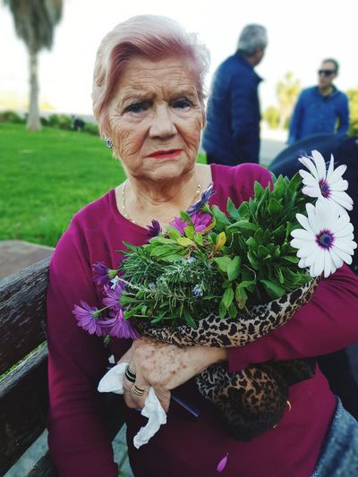 Portrait of woman holding flowers bouquet during event
