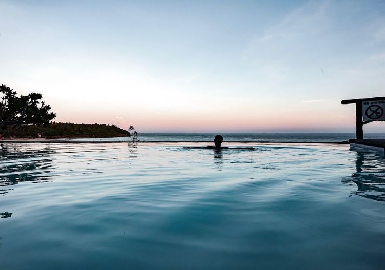 Sun sets. Infinity Pool Infinity Sky Water Beauty In Nature Sea Scenics - Nature Real People Nature Tranquil Scene Waterfront Tranquility Sunset Reflection Silhouette Lifestyles Idyllic Beach Men Outdoors Non-urban Scene