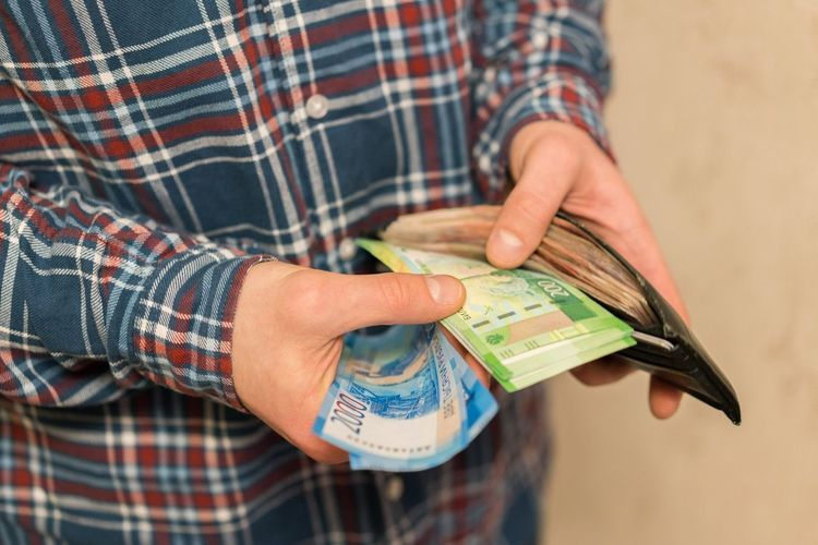Midsection Of Man Removing Paper Currencies From Wallet