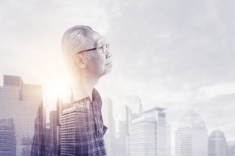 Digital composite image of man looking at cityscape against sky