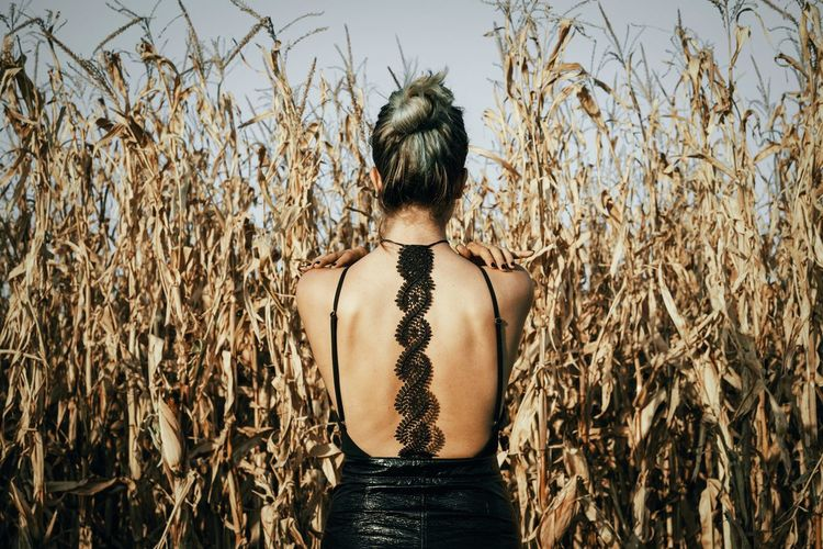 Rear view of woman standing against plants on agricultural field