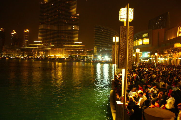 A busy crowd on the lakeside gearing up for a water fountain show! Arabic Architecture Blue Blur Building Exterior Built Structure Burj Khalifa City Crowd Dubai Fountain Dubai Mall Illuminated Lake Large Group Of People Lights Lights In The Dark Night Nightlife Outdoors People Real People Skyscraper Teal Waterfront Yellow Light The Street Photographer - 2017 EyeEm Awards