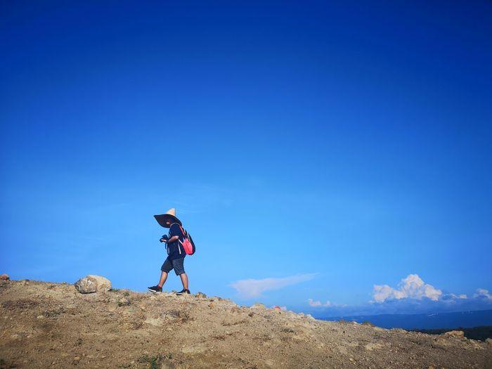Woman wearing hat walking on mountain against blue sky
