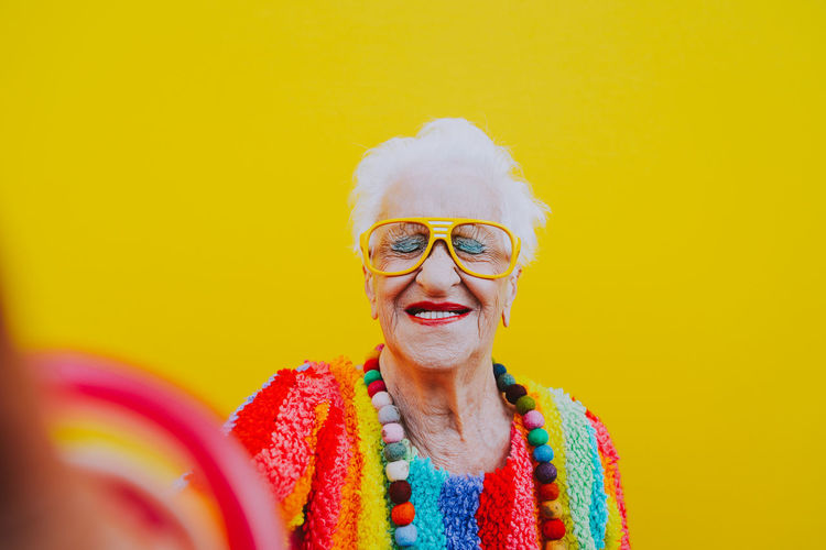 Smiling woman wearing colorful clothing against yellow background