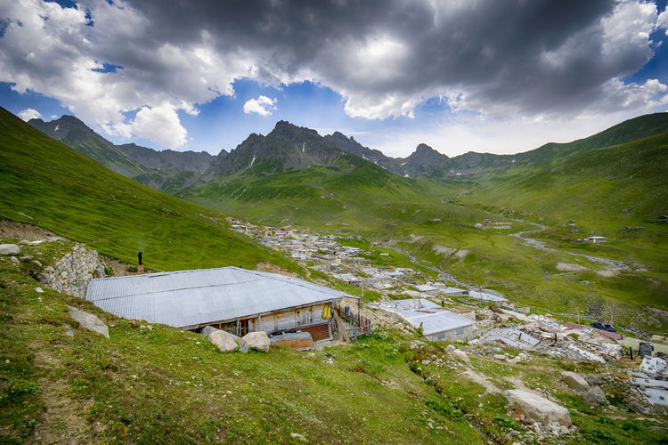 Scenic view of mountains and houses against sky