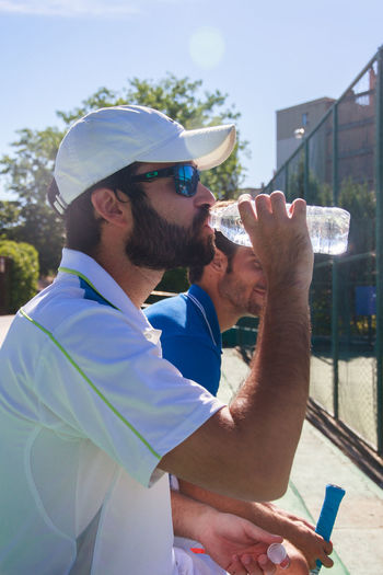Tennis Player Drinking Water With Man While Sitting At Court