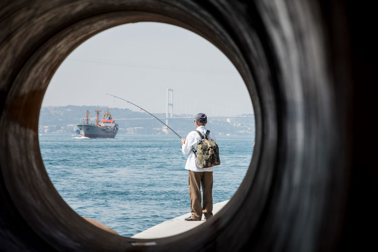 Istanbul Adult Arch Bosphorus Day Fishing Fishing Pole Full Length Horizon Over Water Nature One Person Outdoors People Real People Rear View Sea Sky Standing Water