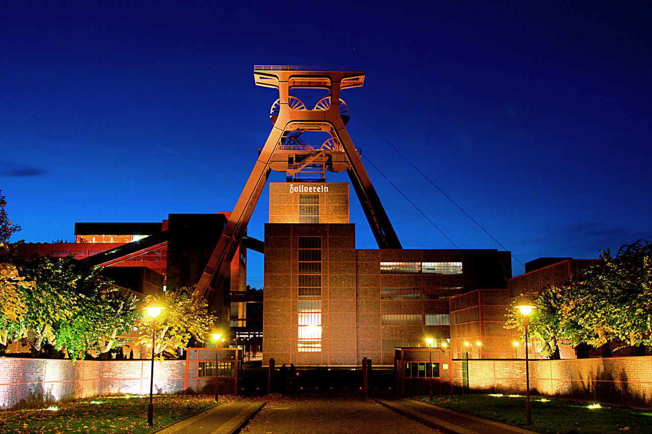 illuminated, sky, night, architecture, built structure, building exterior, no people, nature, blue, tower, dusk, tree, clear sky, lighting equipment, outdoors, low angle view, machinery, industry, building, factory
