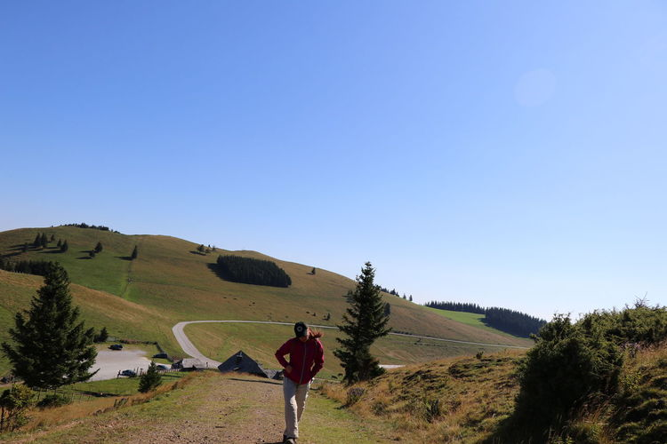 Rear view of man on landscape against clear blue sky