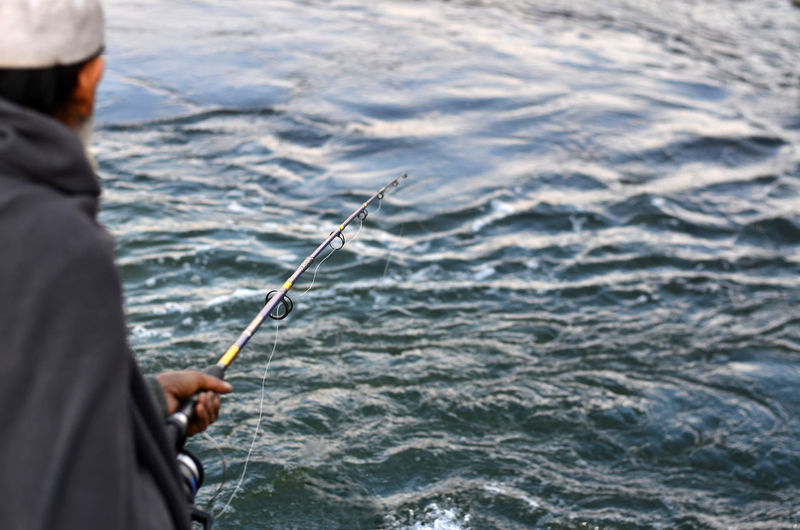 Close-up of man fishing in sea